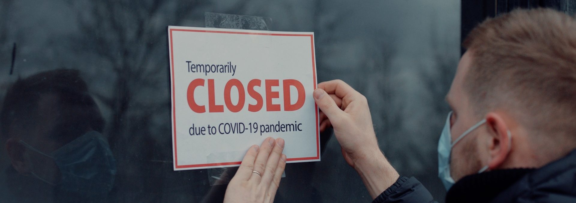 Caucasian male wearing medical mask puts a Temporary closed due COVID-19 pandemic sign on a window. Coronavirus pandemic, small business shutdown